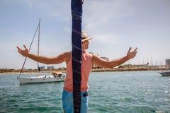 Bemannen Sie Stellung auf einem Bogen des Segelboots mit den angehobenen Armen Stockfotos