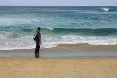 Bemannen Sie Stellung auf einem Strand und das Betrachten des Ozeans Stockbild