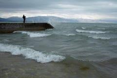Bemannen Sie Stellung auf konkretem Pier in gewelltem Meer Stockfotos