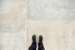 Bemannen Sie Stellung auf konkreter Bodenbelagoberfläche, Füße von oben Lizenzfreie Stockbilder