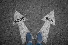Bemannen Sie Stellung auf Straße mit den guten und schlechten Richtungspfeilwahlen Lizenzfreies Stockbild