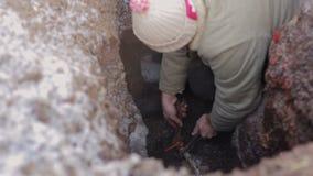 Bemannen Sie Stellung in einem Loch in der Erde und Herstellungsreparatur des Wassersystems Klempner mit überspannt, einen Hahn i stock footage