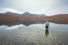 Bemannen Sie Stellung im klaren See, der durch die schottischen Hochländer umgeben wird Stockfoto