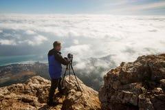 Bemannen Sie Stellung mit einem Stativ und einer Kamera auf einer hohen Bergspitze über Wolken, Stadt und Meer Berufsfotograf Stockfotografie