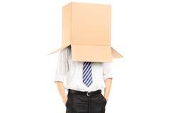Bemannen Sie Stellung mit einer Pappschachtel auf seinem Kopf Lizenzfreies Stockbild