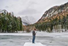 Bemannen Sie Stellung mit kalter Winteransicht, -schnee und -eis am bewölkten Tag Lizenzfreie Stockbilder