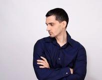 Bemannen Sie Stellung mit seinem Arme gekreuzten Schauen unten über der Schulter zur Seite vom Profil. Lizenzfreies Stockbild