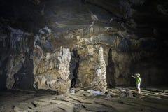Bemannen Sie Stellung neben einer Gruppe der Stalaktithöhle Stockbilder