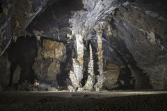 Bemannen Sie Stellung neben einer Gruppe von Stalaktithöhle 3 Stockbild