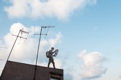 Bemannen Sie Stellung am Rand der Dachspitze mit Karte in den Händen mit hellem blauem Himmel und weißen Wolken am Hintergrund stockbilder