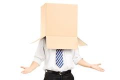Bemannen Sie Stellung und das Gestikulieren mit einer Pappschachtel auf seinem Kopf Lizenzfreies Stockfoto