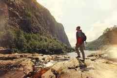 Bemannen Sie Stellung vor einem Felsen in einem Gebirgswasserfall Stockfoto