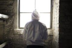 Bemannen Sie Stellung vor einem Fenster in einer Kabine Stockbild