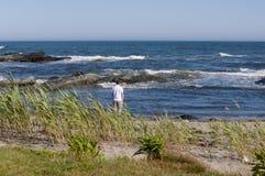 Bemannen Sie Stellung am Wasserrand am Ozeanstrand mit sonnigem blauem Himmel und blauem Wasser Stockfoto