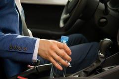 Bemannen Sie am Steuer von einem Auto, nahm eine Flasche Wasser auf der Straße stockfoto