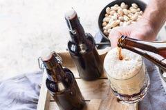 Bemannen Sie strömendes Bier in Glas Lizenzfreies Stockfoto