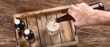 Bemannen Sie strömendes Bier in Glas Lizenzfreie Stockfotos