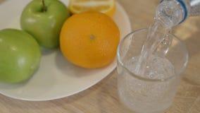 Bemannen Sie strömendes Wasser in Glas bei Tisch mit Frucht im Hauptinnenraum stock video footage