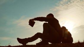 Bemannen Sie Studentenlesung im Park mit Rucksack gegen Sonnenuntergang Schattenbild des Mannlesebuches bei Himmellebensstilsonne stock video footage