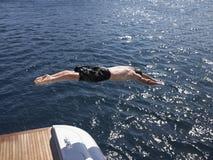 Bemannen Sie Tauchen in Meer von der Yacht Lizenzfreie Stockfotos