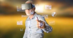 Bemannen Sie tragende Diagramme eines rührende Geschäfts des virtuellen Kopfhörers der Wirklichkeit auf einem Touch Screen Stockfotos