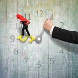Bemannen Sie tragende rote Pfeilbalance auf Geldzeichen-Uhrhänden mit Lizenzfreies Stockfoto