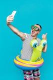 Bemannen Sie tragende Unterwassermaske, das gestreifte Hemd und die Schöße schwimmen, die das Telefon untersuchen und selfie sehr Stockfotografie