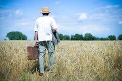 Bemannen Sie tragenden Hut mit dem Koffer, der weg durch geht Stockbilder