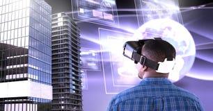 Bemannen Sie tragenden Kopfhörer der virtuellen Realität mit hohen Gebäuden mit Welt und Schirme schließen an Lizenzfreie Stockbilder