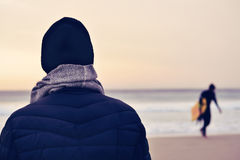 Bemannen Sie tragenden Mantel, Schal und Strickmütze vor dem Ozean lizenzfreie stockfotografie