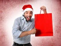 Bemannen Sie tragenden Sankt-Hut, der das Weihnachtseinkaufstaschelächeln glücklich hält Stockfotografie