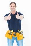 Bemannen Sie tragenden Werkzeuggurt, während das Darstellen herauf Zeichen abgreift Stockbild