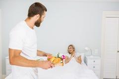 Bemannen Sie tragendes Frühstück für eine Frau im Bett Stockfotos