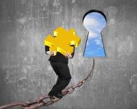 Bemannen Sie tragendes goldenes Puzzlespiel auf Kette in Richtung zum Schlüsselloch mit Himmel Lizenzfreie Stockfotos