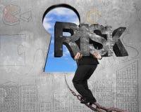 Bemannen Sie tragendes konkretes Wort des RISIKOS auf Kette in Richtung zum Schlüssellochhimmel Stockfotos