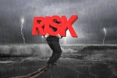 Bemannen Sie tragendes rotes RISIKO-Wort auf Kette mit stürmischem Ozean Stockfotos