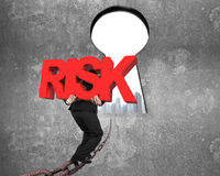 Bemannen Sie tragendes rotes RISIKO-Wort auf Kette in Richtung zum Schlüssellochstadtbild Lizenzfreie Stockfotografie