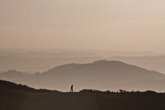 Bemannen Sie Trekking auf einem Berg mit einem dunstigen rosa Hintergrund Stockfotos
