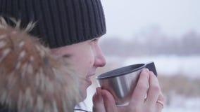 Bemannen Sie trinkenden heißen Tee im Winter draußen im Park Gesunder Lebensstil, draußen gehend Stockfotos
