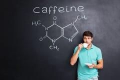 Bemannen Sie trinkenden Kaffee über Tafel mit Struktur des Koffeinmoleküls Lizenzfreies Stockfoto