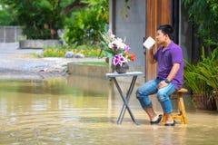 Bemannen Sie trinkenden Kaffee um das Haus während des überschwemmten Hauses und des Fahrzeugs Stockbild
