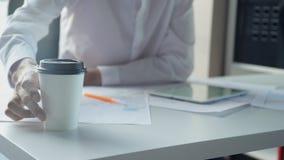 Bemannen Sie trinkenden Kaffee während des Arbeitens unter Verwendung des Laptops im Büro stock footage