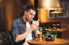 Bemannen Sie trinkendes Bier und rauchende Zigarette an der Bar Lizenzfreie Stockfotografie
