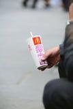 Bemannen Sie trinkendes McDonalds-Soda auf einem stret backgroun Lizenzfreie Stockfotos