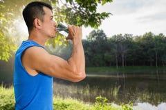 Bemannen Sie Trinkwasser vom Glas nach Übung auf unscharfem Naturhintergrund mit weichem Sonnenlicht lizenzfreie stockfotografie