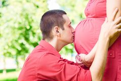 Bemannen Sie Umarmungen und Küsse ein Bauch stockbild
