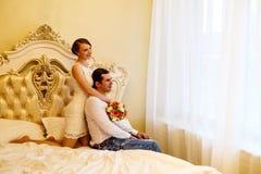 Bemannen Sie und die Frau auf einem Bett mit Blumen schauen aus dem Fenster heraus Lizenzfreie Stockfotos