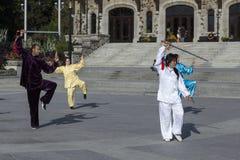 Bemannen Sie und drei Frauen in den asiatischen Ausstattungen teilnehmend an einer Tai Chi-Demonstration stockbild