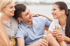 Bemannen Sie und zwei Frauen, die auf Strand mit Bier sich entspannen Lizenzfreies Stockbild