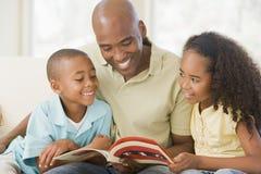 Bemannen Sie und zwei Kinder, die im Wohnzimmer sitzen Lizenzfreie Stockfotos